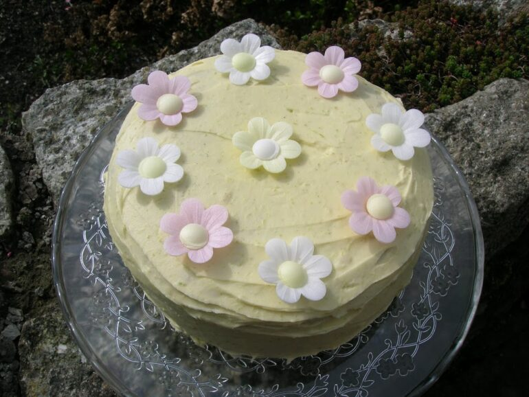 Lime and white chocolate genoise sponge cake covered in lime and white chocolate icing with wafer daisies on the top.