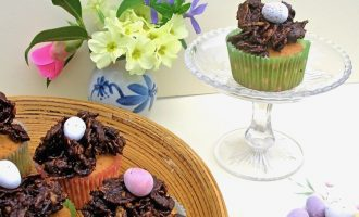 Easter Nest Cupcakes with a plate of mini eggs and a vase of primroses.