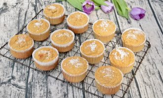 12 Gluten-Free Coconut Cakes on a cooling rack with maybe tulips in the background.