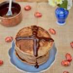 Hot Cross Bun Pancakes for Easter Breakfast or Brunch with chocolate sauce, flowers and mini eggs.