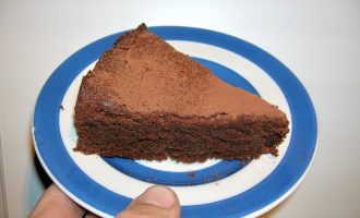 Slice of gluten-free chocolate almond cake on a Cornishware plate.