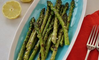 Turquoise serving plate with griddled asparagus, lemon halves with napkins and forks at the ready.
