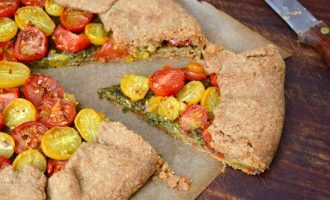 Slice of rustic tomato galette with homemade basil pesto.