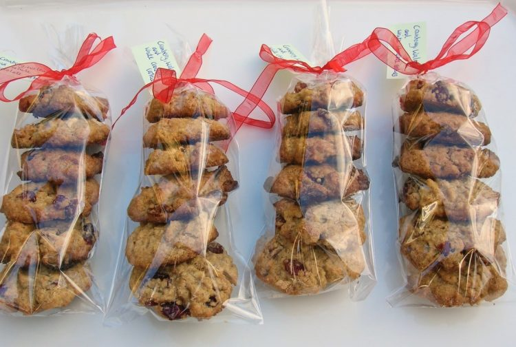 Cranberry White Chocolate Cookies with Walnuts packed into bags and tied with red ribbons as festive gifts.