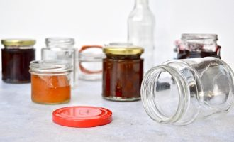 An array of glass jars, both full and empty, to illustrate how to sterilise glass jars.