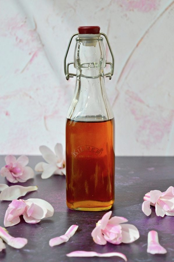 Bottle of Magnolia Syrup with magnolia blossoms.