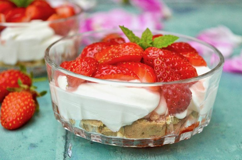 A bowl of strawberries and cream summer dessert.