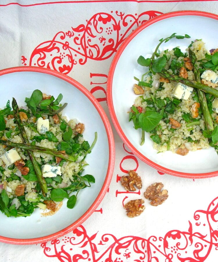 Two bowls of quinoa salad with watercress, walnuts, blue cheese and roasted asparagus.