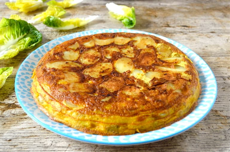 A whole easy Spanish tortilla on a blue plate with lettuce leaves in the background.