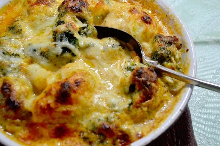 A dish of broccoli cauliflower cheese with serving spoon embedded.